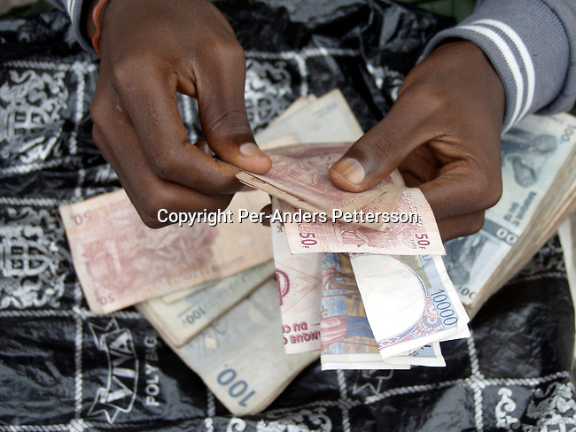 KINSHASA, CONGO - FEBRUARY 28: An unidentified man counting Congolese Francs in the street on February 28, 2002 in central Kinshasa. He works as a money changer changing the Congolese Franc for about 330 to one $..Photo: Per-Anders Pettersson/ Getty Images....