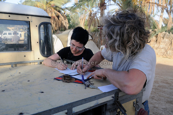 Africa, Tunisia, Douz. Desert travellers Kerstin and Stephan doing official paperwork at the campground in Douz. --- No releases available, but releases may not be needed for certain uses. Automotive trademarks are the property of the trademark holder, authorization may be needed for some uses.  --- Info: Image belongs to a series of photographs taken on a journey to southern Tunisia in North Africa in October 2010. The trip was undertaken by 10 people driving 5 historic Series Land Rover vehicles from the 1960's and 1970's. Most of the journey's time was spent in the Sahara desert, especially in the area around Douz, Tembaine, Ksar Ghilane on the eastern edge of the Grand Erg Oriental.