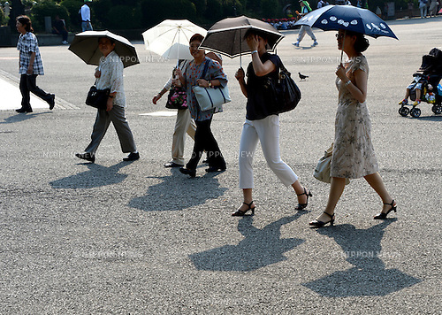 July 27, 2012, Tokyo, Japan - Japanese women make vain efforts to screen themselves from the scorching summer sun with parasols at Tokyos Ueno Park as a powerful high-pressure system in the Pacific Ocean continues to cover much of Japan with a prolonged searing heat wave on Friday, July 27, 2012..Four people died and 916 were hospitalized for heatstroke Thursday as the mercury rose as high as 38 degrees Celcius in Gifu Prefecture. The Japan Meteorological Agency warned of continued high temperatures nationwide in the coming two weeks and in most regions throughout August. (Photo by Natsuki Sakai/AFLO)..