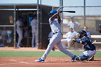 AZL Royals left fielder David Hollie (11) follows through on his swing in front of catcher Rainier Aguilar (8) during an Arizona League game against the AZL Padres 1 at Peoria Sports Complex on July 4, 2018 in Peoria, Arizona. The AZL Royals defeated the AZL Padres 1 5-4. (Zachary Lucy/Four Seam Images)