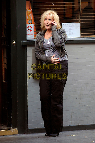 BEVERLEY CALLARD .Outside the Groucho Club, Soho, London, England..April 13th, 2010. **EXCLUSIVE ALL ROUNDER**.full length black grey gray trousers cardigan talking on mobile phone.CAP/IA.©Ian Allis/Capital Pictures.