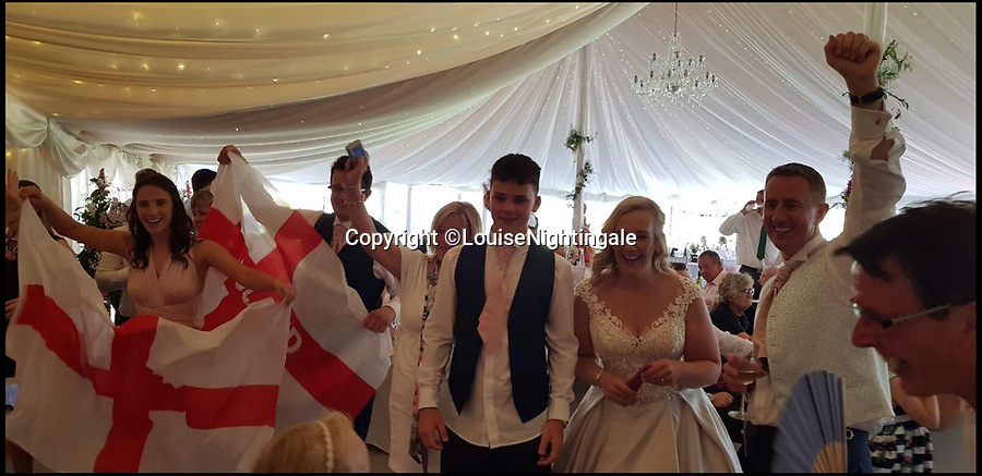BNPS.co.uk (01202 558833)Pic: LouiseNightingale/BNPSThe newlywed couple watch the second half together.Match of the day...A newlywed couple kept football fans at their wedding happy by showing England's game while they had their wedding breakfast.Just married Louise Nightingale and Tony Oram organised a big projector and screen in their wedding marquee to show the quarter final as they sat down for the formal dinner.Initially their 75 guests politely craned their necks to watch the action unfold from their seats but as things heated up everyone crowded round the screen to see England romp to victory.The couple said they were inundated ahead of the game with requests from friends and family to find a way of making the game available at their reception.