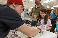 Aliy Zirkle signs an autograph for a youngster as all the mushers who've finished the race as of Saturday March 21st are on hand at the Nome Mini-Convention Center to sign autographs for race fans during Iditarod 2015.  <br /> <br /> (C) Jeff Schultz/SchultzPhoto.com - ALL RIGHTS RESERVED<br />  DUPLICATION  PROHIBITED  WITHOUT  PERMISSION