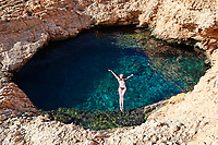 Young woman swim in the natural swimming pool Pissina of Koufonissi island, Greece