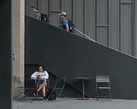 NWA Democrat-Gazette/SPENCER TIREY    Anna Meadows a sophomore at the University of Arkansas sit outside Champion Hall on the Fayetteville campus, Friday Sept. 8, 2018, talking to her mother as other students enter the building.