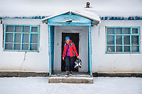 A woman skier traveling in Kyrgyzstan leaving a private home