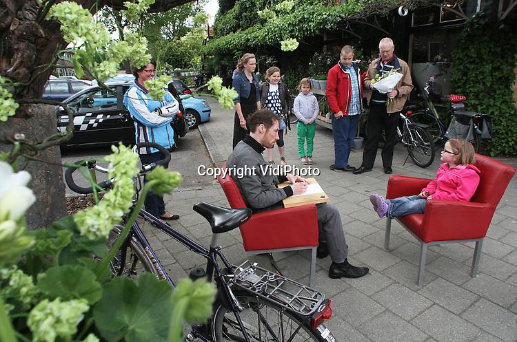Foto: VidiPhoto..VEENENDAAL - Een portrettekenaar zorgde zaterdag voor extra drukte bij bloemenwinkel Meent & Bouman in Veenendaal. Kinderen konden gratis geportretteerd worden bij de aankoop van een moederdagcadeau bij de Veenendaalse bloemist, die het daardoor drukker had dan ooit. De Veenendaler heeft inmiddels landelijke bekendheid door zijn acties als een bloementaart voor koningin Beatrix en het projecteren van oranje lampen op een witte kerk in Veenendaal tijdens Koninginnedag..