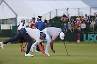 Brooks Koepka (USA) and Jason Day (AUS) do some housekeeping on the 8th green during Friday's Round 2 of the 118th U.S. Open Championship 2018, held at Shinnecock Hills Club, Southampton, New Jersey, USA. 15th June 2018.<br /> Picture: Eoin Clarke | Golffile<br /> <br /> <br /> All photos usage must carry mandatory copyright credit (&copy; Golffile | Eoin Clarke)