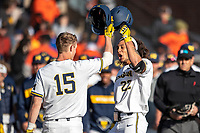 Michigan Wolverines outfielder Jordan Brewer (22) is greeted at the plate by teammate Jimmy Kerr (125) after his first inning home run against the Rutgers Scarlet Knights on April 26, 2019 in the NCAA baseball game at Ray Fisher Stadium in Ann Arbor, Michigan. Michigan defeated Rutgers 8-3. (Andrew Woolley/Four Seam Images)