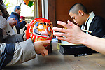 March 3, 2012, Tokyo, Japan - A woman handed a Daruma doll, a Japanese traditional ornament of Buddhism, to a priest to get an eye on it as begging of this year's happiness at Daruma Ichi, or Daruma Market, at Jindaiji Temple in Chofu, Tokyo, Japan on March 3, 2012. This was one of the biggest three Daruma Markets in Japan. Since it was taken place on March 3 and 4 every year no matter what day of the week and was weekend this year, many people showed up. (Photo by Koichiro Suzuki/AFLO) [4012]