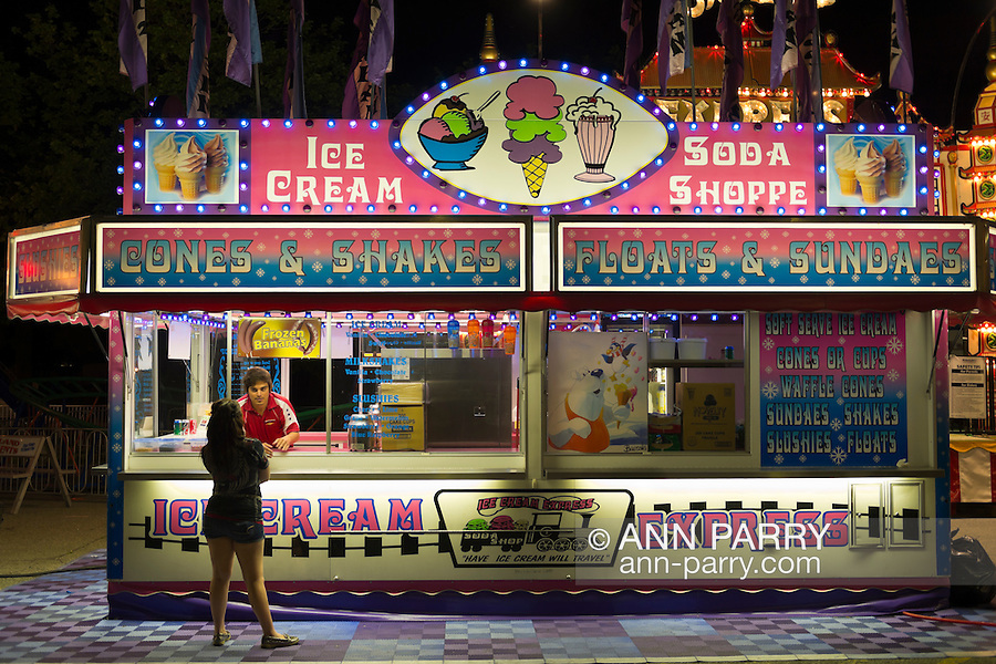 A carnvial worker in Ice Cream Express booth is speaking with young woman at the food order window, on the first day of the annual Herricks Community Fund Spring Carnival, which raises funds for programs that enrich the community and school district. The Long Island carnival runs through June 2.