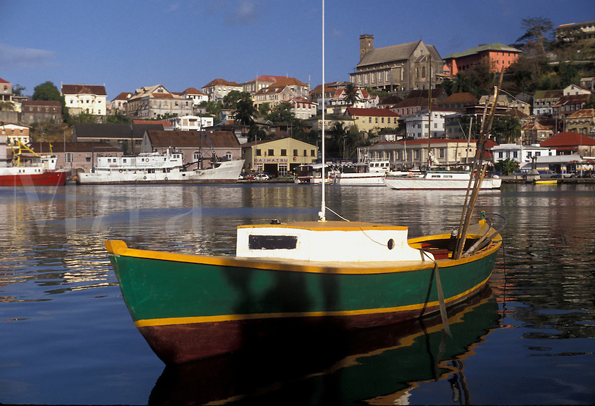 """AJ2526, Grenada, Caribbean, St. George's, Caribbean Islands, Green fishing boat anchored in the calm waters of the Carenage Harbor with a scenic view of St. George's the capital city on the steep hillside on the island of Grenada """"""""the spice isle"""""""" (a British Commonwealth member)."""