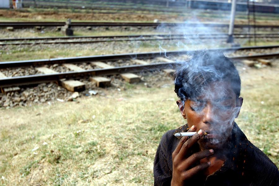 2006. Bangladesh, Dhaka. A young drug user smokes marijuana at a railway station. .Drug abuse is getting popular even among the very young...2006. Bangladesh, Dhaka. Un jeune consommateur de drogue fume de la marijuana sur un chemin de fer..Les abus de drogue deviennent en vogue chez les très jeunes.