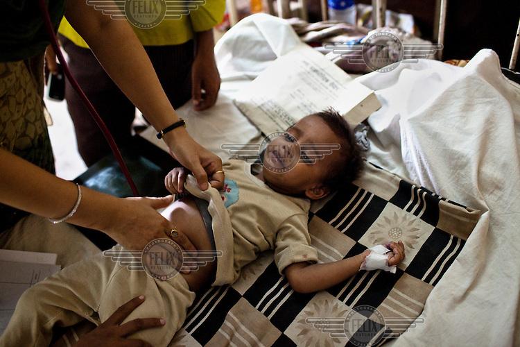 A doctor checks the abdomen of a sick child in the pediatric ward at Maharani Laxmibai Medical College in Jhansi.