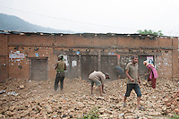 Nepalese people clear the rubble from their destroyed house in the earthquake near at Kathmandu, Nepal. May 8, 2015