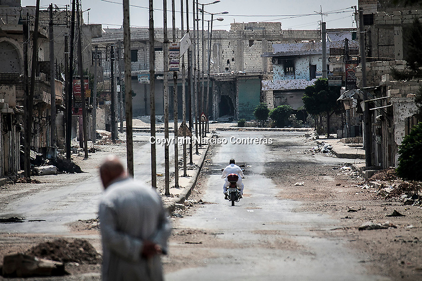 Syrian civilians walk among the ruins of the Al Atarib town. The city was flattened during months of shelling by the Syrian army, turning the city of 30,000 inhabitants into a ghost town of only 300, as the army was trying to sweep out the rebels. Today, Al Atarib belong to the FSA controlled territory, but it still being watched by the Syrian army and bombed occasionally.