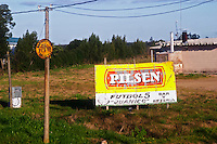An old rusty billboard advertising sign in Juanico publicizing Pilsen beer and the Futbol 5 Bar and Pizzeria. Uruguay, South America