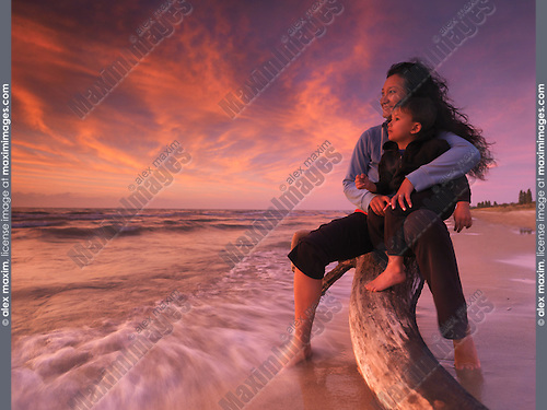 Portrait of a happy smiling woman and a child watching beautiful colorful sunset over lake Huron. Ontario, Canada.