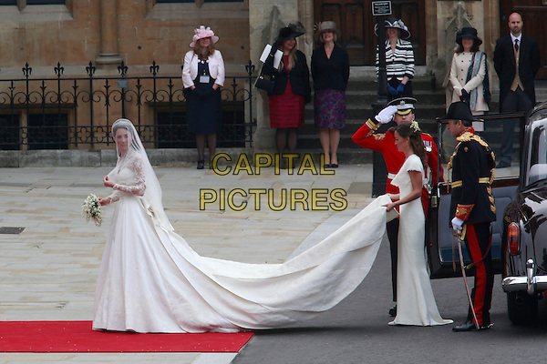 KATE MIDDLETON soon to be CATHERINE, DUCHESS OF CAMBRIDGE & PIPPA MIDDLETON.At her Royal Wedding to Prince William , Westminster Abbey, London, England 29th April 2011.Kate Middleton royals royalty full length sisters siblings family dress train veil white holding flowers bouquet.CAP/PE..©Peter Eden/Capital Pictures..