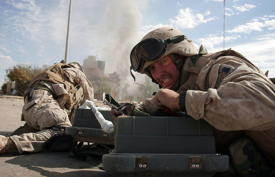 A pair of Marine combat engineers - attached to Golf Co. 2nd Battalion 1st Marines - lies in the middle of a street totally exposed to insurgent gunfire as it rushes to employ a rocket-fired mine and IED clearing device to make a breach for the company to push forward and take a group of houses from which it had been receiving sniper fire during the second day of Operation Steel Curtain, an operation to clear Husaybah (a city on the Iraq-Syrian border) of insurgents on Sun. Nov. 6, 2005. The operation, which has been labeled by the US military as one of the largest since the assault on Fallujah in Nov. 2004, involves more than 2,500 US personnel and 1,000 Iraqis.