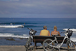 Couple watching surfers with bikes proped against their seat, Playa de la Americas.Tenerife, Canary Islands