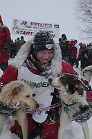 Second place finisher Ben Lyon congratulates his lead dogs at the finish line of the Junior Iditarod on Willow Lake in Willow, Alaska.  Ben came in second just one minute behind first place winner Conway Seavey.