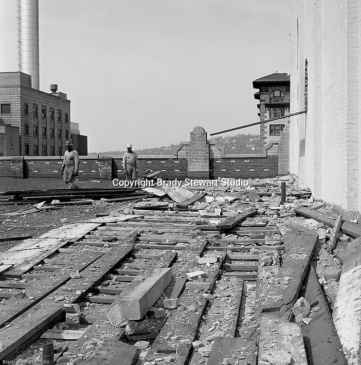 Pittsburgh PA:  View of the building demolition of one of downtown Pittsburgh's grand department stores, Rosenbaums. Construction workers pulling roof planks up.  Located at Penn Avenue and Sixth Street in Pittsburgh, the store closed in 1960 and taken down in 1963 to make way for the Sixth Avenue garage.  The demolition work was completed by D&H Building Wreckers.