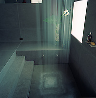 Steps lead down to the sunken shower which is equipped with a large and powerful shower head