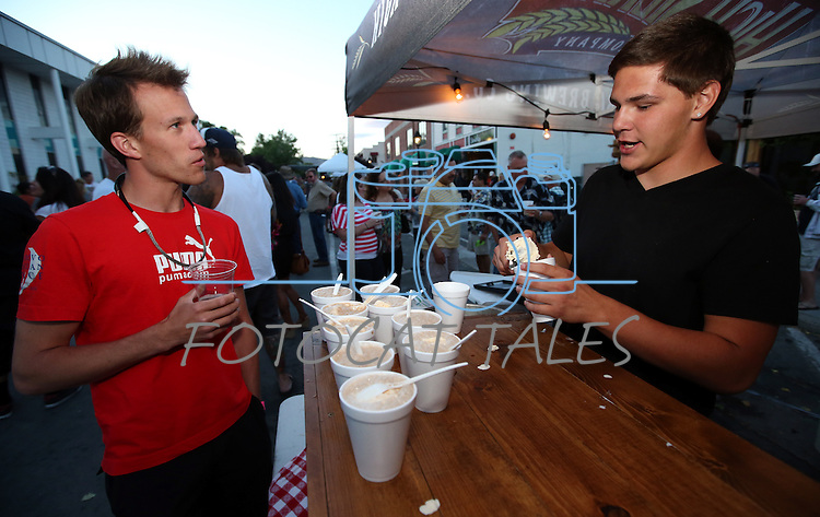 Adam (declined to provide last name but OK with photo usage) talks with Joey Moore as he makes root beer floats at the High Sierra booth during the 20th annual Taste of Downtown event in Carson City, Nev., on Saturday, June 15, 2013. The event features 44 local restaurants in a fundraiser for the Advocates to End Domestic Violence.<br /> Photo by Cathleen Allison