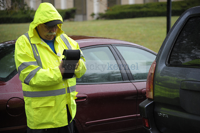 John Reed a Parking Control Officer for the University of Kentucky writes a ticket for an illegally parked vehicle. Photo by Mike Weaver | Staff