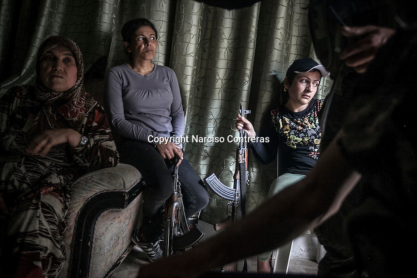 "Kurdish women, female members of the ""Popular Protection Units"" (YPG), sit inside a house in the majority-Kurdish Sheikh Maksoud district that they patrol and protect as clashes continue after Syrian opposition fighters entered into the Kurdish area forcing thousands of civilians to flee into safe areas outside of Aleppo City. Since then, the neighborhood is being bombed and shelled by Syrian forces in its attempt to sweep out the opposition fighters from the area."