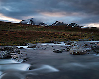 Flowing river outside of Syter hut with mountains of Norra Stofjället in background, Kungsleden trail, Lapland, Sweden