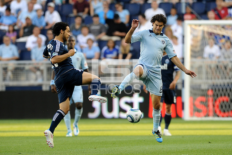 Davide Chiumiento (navy) Vancouver Whitecaps tassles for the ball in midfield with Sporting KC midfielder Graham Zusi... Sporting KC defeated Vancouver Whitecaps 2-1 at LIVESTRONG Sporting Park, Kansas City, Kansas.