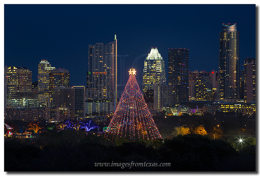 The Zilker Park Christmas Tree rises into the night as Austin celebrates Christmas with the annual Trail of Lights. In the background shines the Austin skyline with its iconic buildings, the Frost Bank Tower and the Austonian. <br />