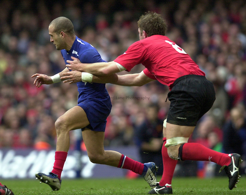 Photo. © Peter Spurrier/Richard Lane Photography.07/03/2004 Six Nations Rugby - Wales v France.Wales No. 8 Dafydd Jones moves in to tackle Frederic Michalak....