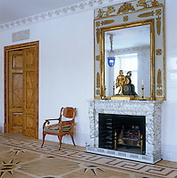 The focal point of this living room in St Petersburg is a large fireplace of grey-veined marble topped with an ornate gilded mirror and ormolu clock
