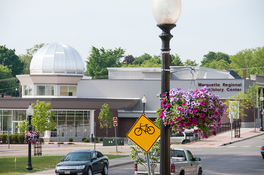 View of Third Street in downtown Marquette Michigan with the Marquette Regional History Center, bike path signage and flower baskets in spring summer.