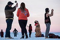 People, including one dressed as a dinosaur, look at the sunset from atop dunes at White Sands National Monument near Alamogordo, New Mexico, on Dec. 30, 2017.