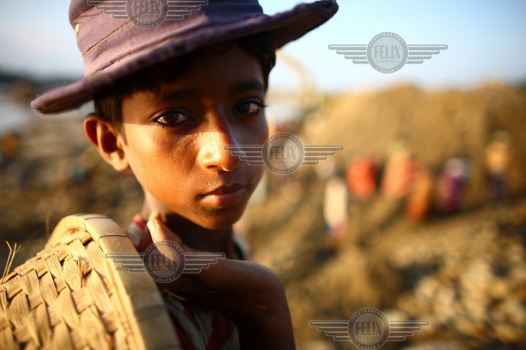 A child worker at Bhollar Ghat. At least 10,000 people, including 2,500 women and over 1,000 children, are engaged in stone and sand collection from the Bhollar Ghat on the banks of the Piyain river. Building materials such as stone and sand, and the cement which is made from it, are in short supply in Bangladesh, and commands a high price from building contractors. The average income is around 150 taka (less than 2 USD) a day.