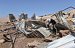 A Palestinian woman stands on the debris of her possessions after it was destroyed allegedly by Israeli army tractors on Sep. 16, 2013 in the West Bank of desolate Makhoul in east of Tubas city. The house was located in the so-called Area C, a closed military zone where Israel exercises full control and was built without permission, according to the Israeli army. Photo by Nedal Eshtayah