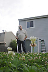 Mikhail Mazo, 52, a Russian immigrant, stands in his backyard after he received a warning notice for not trimming his lawn from the suburban Chicago municipality of Buffalo Grove, Illinois on July 2, 2009.