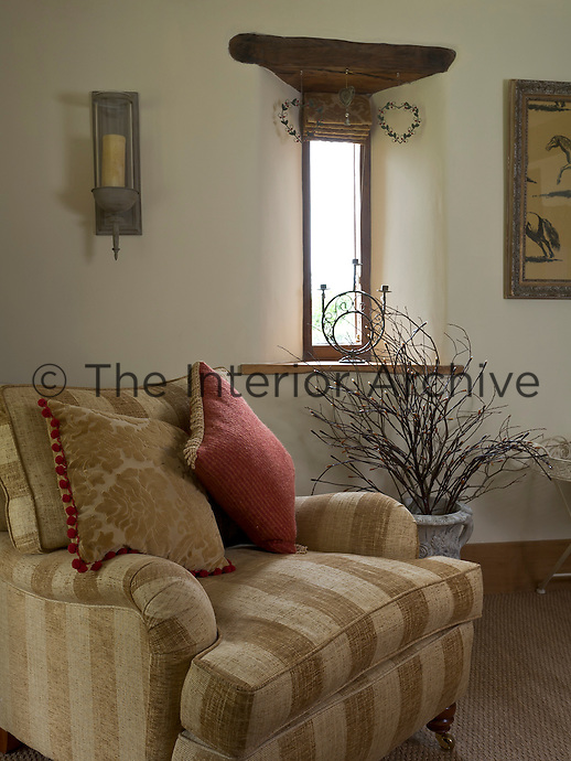In a corner of the living room a comfortable armchair is covered in a muted coffee and beige striped linen and piled with a collection of scatter cushions