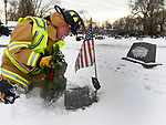 Ellington Volunteer firefighter Randy Smith, places a wreath on the grave of  Saturday, December, 16, 2017,during a Wreaths Across America event in Ellington, Saturday, December, 16, 2017, The local event was sponsored by the Ellington Fire Department who places more than 100 wreaths on the graves of veterans. (Jim Michaud / Journal Inquirer)Vernon.