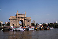 Tourist ferries crowd the Gateway to India monument that faces the Arabian sea on the Marine Drive in Mumbai, India. Photo by Suzanne Lee