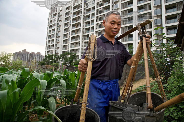 A former farmer supplements his living as a new urbanite by growing vegetables on land that has been claimed by the government to build relocation housing project in the southwestern Chinese megapolis of Chengdu. He and his neigbours were all moved from their farmland and resettled nearby in this purpose-built estate. Some bemoan the poor relocation compensation but others are happy to enjoy a social life away from the burden of farming. The Chinese government plans to move 250 million rural residents into urban areas over the coming dozen years though it is unclear whether people want to move and where the money for this project will come from. Further urbanisation is meant to drive up consumption to counterbalance an export orientated economy and end subsistence farming but the drive to get people off the land is causing tens of thousands of protests each year. /Felix Features