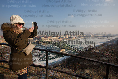 Woman takes a selfie in Gellert hill with the ice blocks floating on river Danube in the background in Budapest, Hungary on January 10, 2017. ATTILA VOLGYI