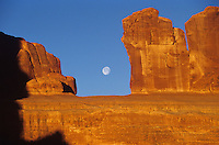 moon through slot in red cliff at sunsise-Arches National Park, Utah