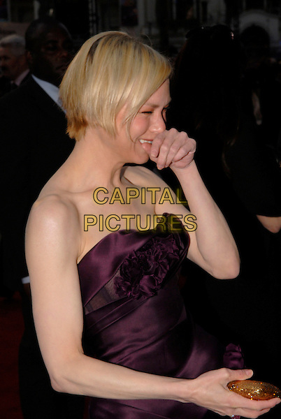"RENEE ZELLWEGER .Attending the ""Leatherheads"" European Film Premiere held at the Odeon cinema, Leicester Square London, England, 8th April 2008..half length strapless purple plum aubergine ruffle front hand touching nose face funny .CAP/IA.©Ian Allis/Capital Pictures"