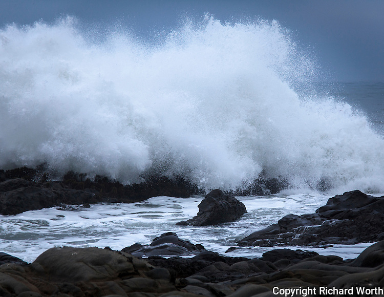 A wave crashes into the rocky Pacific coast at Bean Hollow State Beach.