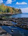 Split Rock Lighthouse SP, MN<br /> Clouds and blue sky reflect in small pools on the rocky shoreline of Lake Superior with fall forests and Split Rock Lighthouse in the distance